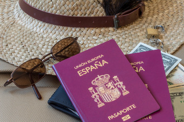 Tourism travel concept. Spanish passports, female hat, sunglasses, and money