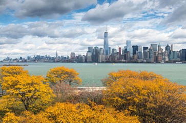 View of Downtown Manhattan from Ellis Island with autumnal trees