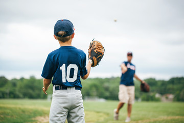 Baseball player playing with his father on field