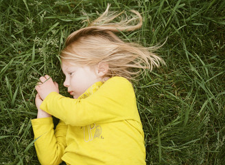 Little Girl in a Yellow Shirt Lays in the grass While Clasping Her Hands