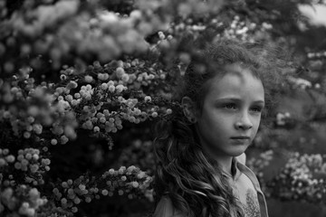 Moody portrait of a young girl amongst blossoms