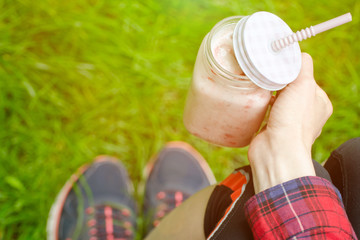 Strawberry smoothies in hand and sneakers on a background of green grass