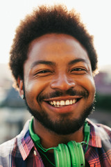Closeup portrait of a young african american man smiling outside.
