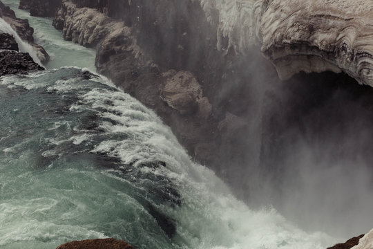 water rushing over an icy waterfall and falling into a gorge