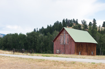 Old red barn near treed ridge, with rustic farm equipment.