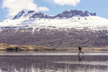 Man running on a narrow sand strip in the  ocean of Eastern Iceland.