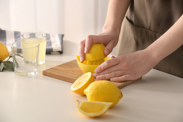Woman preparing lemonade in kitchen, closeup