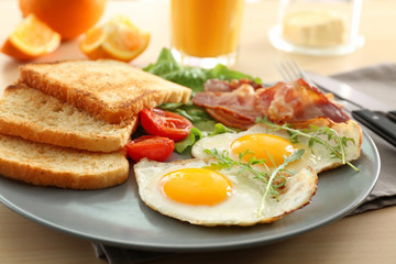 Tasty breakfast with fried eggs on table