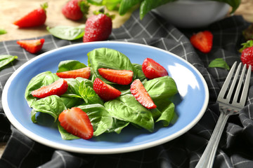 Tasty salad with spinach and strawberry on plate