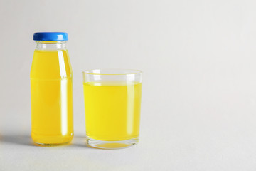 Bottle and glass with delicious juice on light background