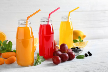 Delicious juices in bottles and fruits on wooden table