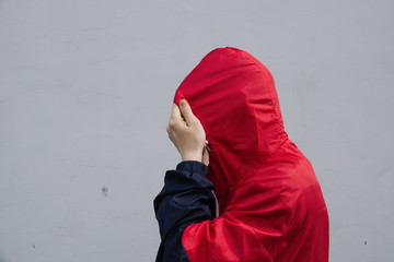 The man puts on the hood on wall background. Natural. Faceless man in hood