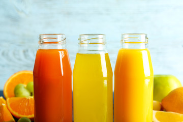 Delicious juices in bottles and fruits on light background