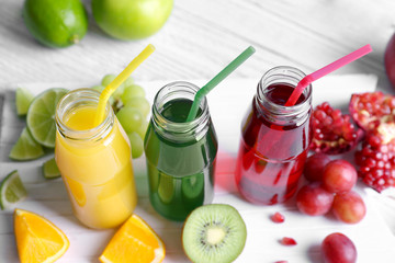 Delicious juices in bottles and fruits on wooden board