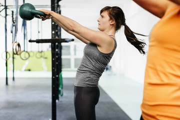 Female Athlete Swinging Kettlebell During Workout Session