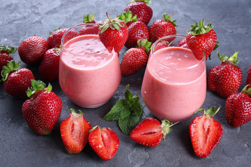 Delicious strawberry homemade smoothie in glasses on grey background