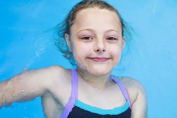 Happy little Girl in bikini swimming pool