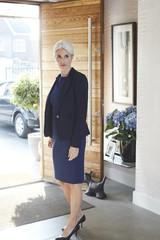Mature businesswoman standing at open door.