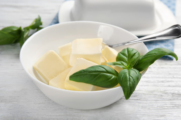 Bowl with cubes of butter and basil leaves on light table