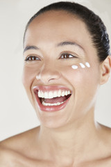 Woman with face cream on cheek, laughing.