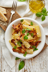 Rigatoni pasta with chanterelle mushrooms, parmesan cheese and fresh basil on a white plate, top view