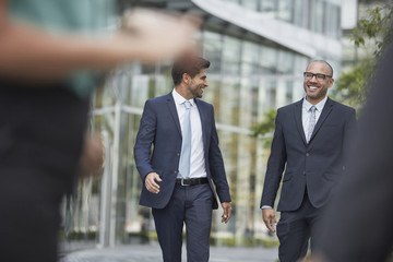 Smiling businessmen walking together