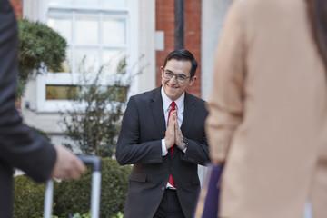 Concierge greeting businesspeople