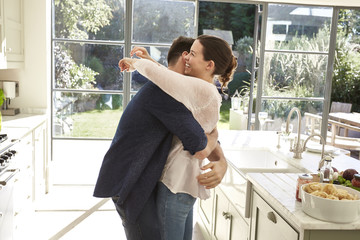 Mid adult married couple hugging in kitchen.