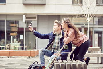 Young couple taking selfie in street