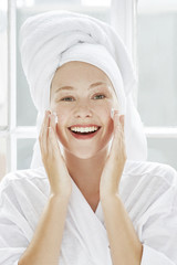 Portrait of young woman applying moisturiser to face.