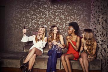 Friends taking selfie on sofa at nightclub