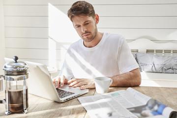 Mid adult man using laptop.