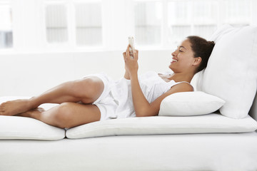 Woman lying on sofa using cell phone.