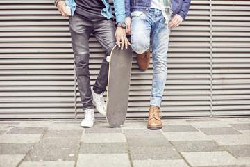 Legs of teenage boys and skateboard