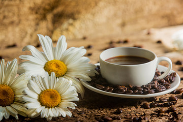 Coffee. A cup of coffee with grains on a wooden background