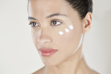 Woman with face cream on cheek.