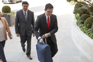 Concierge carrying luggage for businessmen
