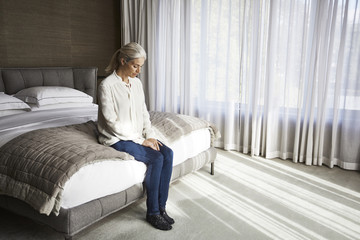 Woman sitting on bed in hotel room