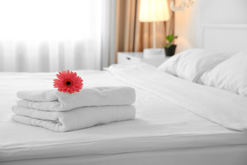 Flower on stack of towels in light hotel room Wall mural