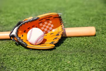 Baseball ball, glove and bat on fresh green grass outdoors