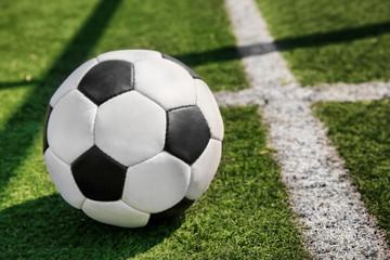 Soccer ball on fresh green grass outdoors