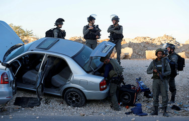 Israeli forces gather near a suspicious Palestinian car near Qalandiya checkpoint, near the West Bank city of Ramallah