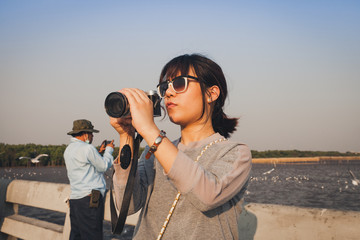 Beautiful asian woman talking picture of seascape and birds in Bang pu seaside, Thailand.