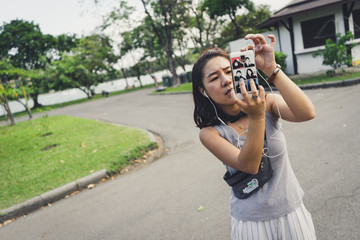Woman take picture in the public park near Bangkok.