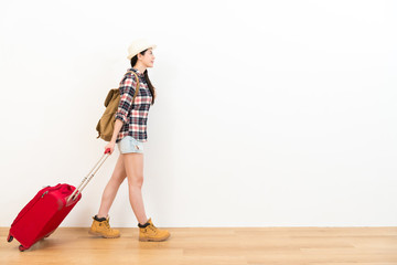 smiling young female traveler pulling red suitcase