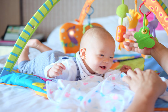 Cute little Asian 5 - 6 months old  baby boy child at tummy time on the play gym playing with his Daddy on Bed in Bedroom at Home