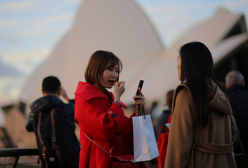 A tourist holding a shopping bag applies make-up before taking a picture in front of the Sydney Opera House in Circular Quay in Sydney, Australia