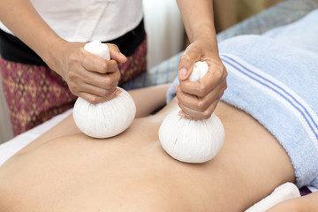 woman back with bamboo mat in spa salon is having massage, Spa, health and healing concept.