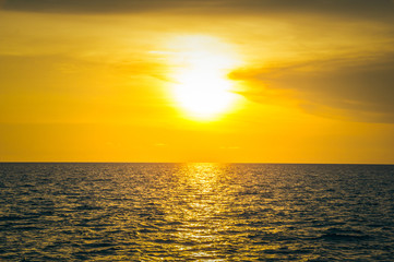 Beautiful blazing sunset landscape at black sea and orange sky above it. Amazing summer sunset view on the beach.