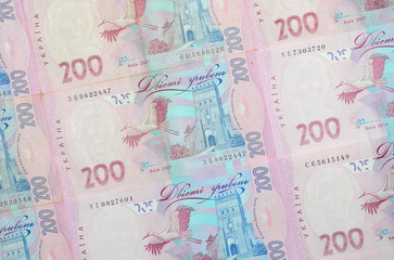 A close-up of a pattern of many Ukrainian currency banknotes with a par value of 200 hryvnia. Background image on business in Ukraine